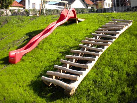 Baumstammtreppe und rote Rutsche
