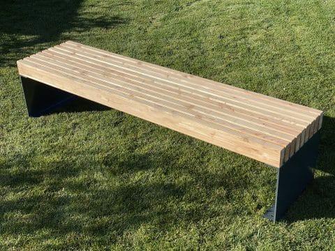Holzbank mit Metallfüßen im Gras