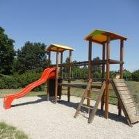Spielplatzanlage mit doppelturm, Wippe, Karusell, Pergola, Reck und Wasserspiele