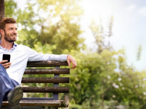 Mann auf Holzbank im Grünen