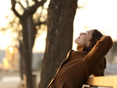 Frau auf Holzbank in der Natur